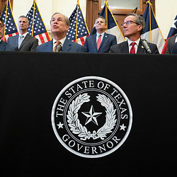 Texas Gov. Greg Abbott (third from right) talks to the press after signing two bills strengthening the Texas power grid and infrastructure that were emergency items on his legislative agenda. The bills were in response to February's winter storm that nearly knocked out the Texas power grid.  At left is Rep. Chris Paddie, R-Marshall, at right, Sen. Kelly Hancock, R-North Richland Hills.