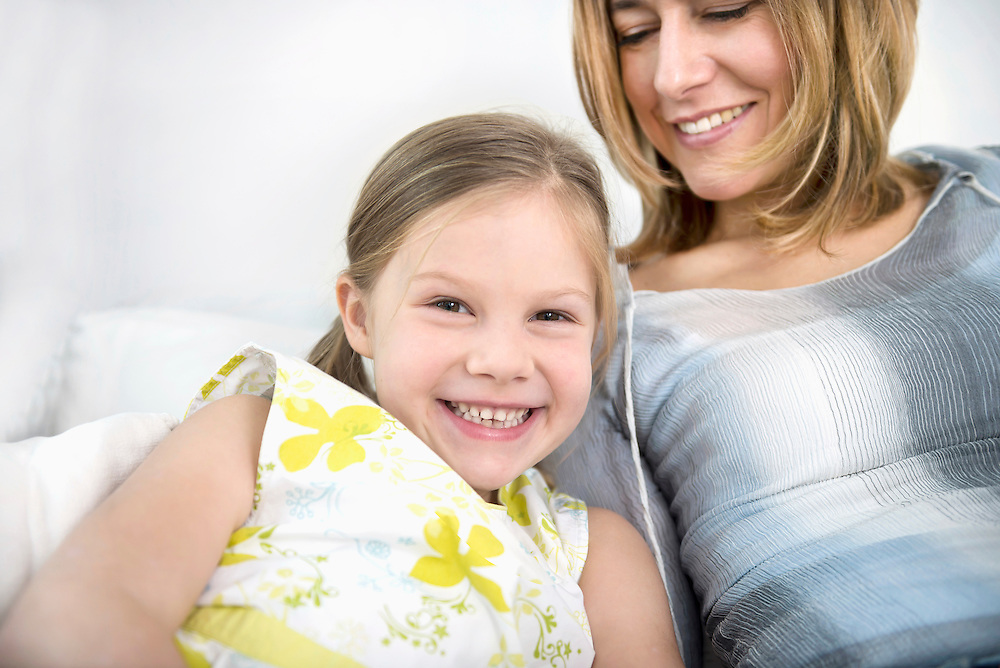 Mother and daughter sitting on sofa, smiling