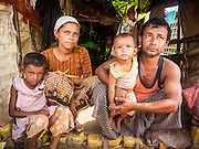 07 NOVEMBER 2014 - SITTWE, RAKHINE, MYANMAR: Rohingya Muslim family AR JEDA, her husband, MAY RALEY, and their children, SHEHAY RA, 7 years old, and NOOR RAKESS, 1.5 years old, in their hut in a Rohingya IDP camp near Sittwe. Noor was born in the camp. After sectarian violence devastated Rohingya communities and left hundreds of Rohingya dead in 2012, the government of Myanmar forced more than 140,000 Rohingya Muslims who used to live in and around Sittwe, Myanmar, into squalid Internal Displaced Persons camps. The government says the Rohingya are not Burmese citizens, that they are illegal immigrants from Bangladesh. The Bangladesh government says the Rohingya are Burmese and the Rohingya insist that they have lived in Burma for generations. The camps are about 20 minutes from Sittwe but the Rohingya who live in the camps are not allowed to leave without government permission. They are not allowed to work outside the camps, they are not allowed to go to Sittwe to use the hospital, go to school or do business. The camps have no electricity. Water is delivered through community wells. There are small schools funded by NOGs in the camps and a few private clinics but medical care is costly and not reliable.   PHOTO BY JACK KURTZ