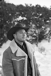 portrait of a rugged cowboy in a shearling coat outdoors