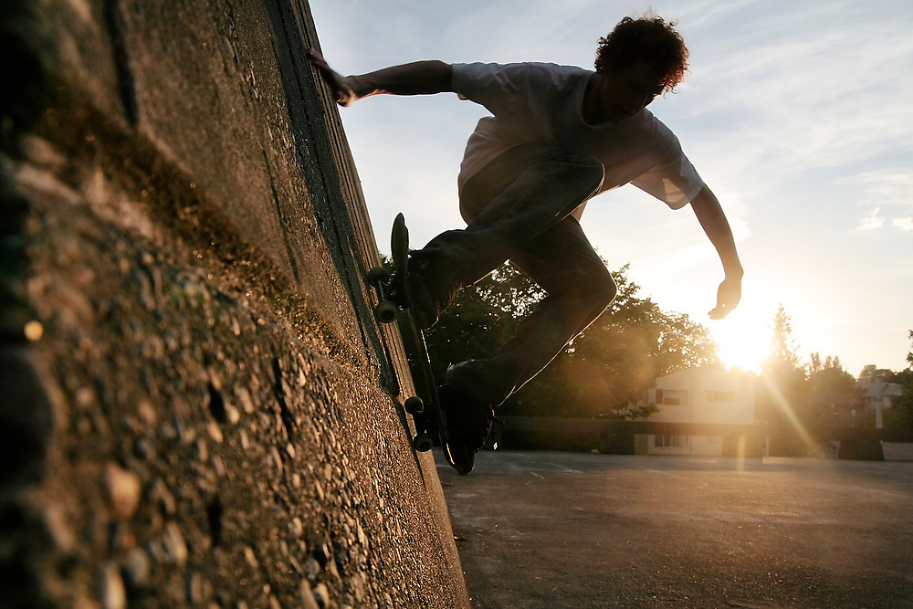 Trevor Fenner rides up a vertical concrete wall on his skateboard during a session on the angular concrete features by Garfield High School in Seattle, Washington
