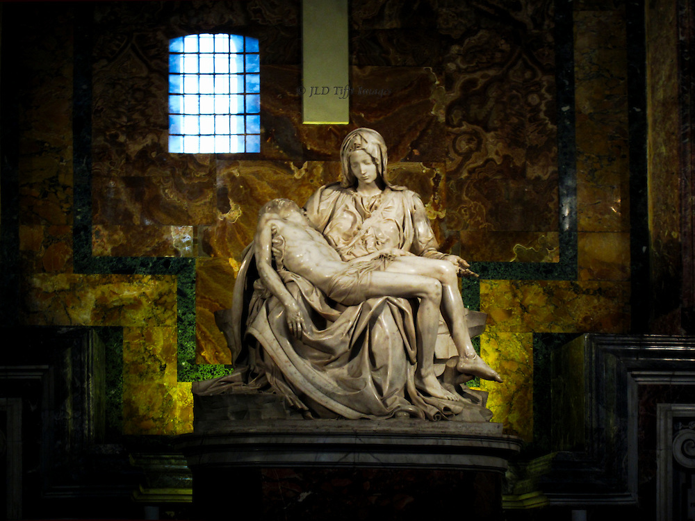 St. Peter's Basilica: Michelangelo's Pieta behind protective glass, with barred window on the other side of the church reflected in the glass.  Multicolor marble sheets on the walls and on the base of the statue add warmth and atmosphere.
