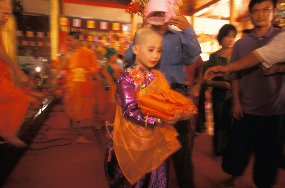 On the final day of the Poy Sang Long, the ordination of novice monks, family members help the boys put on their orange robes, Mae Hong Son, Thailand.