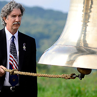 """Paul Murdoch, architect of the Flight 93 National Memorial rings the """"Bells of Remembrance"""" as the name of the passenger and crew are read at the 14th Observance  of Flight 93 Crash and Terrorist Attacks on America near Shanksville, Pennsylvania on September 11, 2015.  Photo by Archie Carpenter/UPI"""