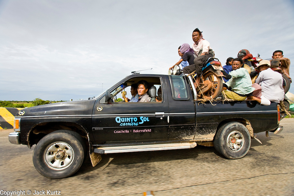 29 JUNE 2006 - KAMPONG THOM, CAMBODIA: A truck being used as a bus hauls passengers through Kampong Thom province in central Cambodia. Photo by Jack Kurtz