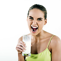beautiful brunette  woman on white background holding a glass of milk