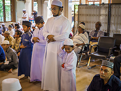 June 25, 2017 - Bangkok, Bangkok, Thailand - A family prays together in Ton Son Mosque before Eid al-Fitr services. Eid al-Fitr is also called Feast of Breaking the Fast, the Sugar Feast, Bayram (Bajram), the Sweet Festival or Hari Raya Puasa and the Lesser Eid. It is an important Muslim religious holiday that marks the end of Ramadan, the Islamic holy month of fasting. Muslims are not allowed to fast on Eid. The holiday celebrates the conclusion of the 29 or 30 days of dawn-to-sunset fasting Muslims do during the month of Ramadan. Islam is the second largest religion in Thailand. Government sources say about 5% of Thais are Muslim, many in the Muslim community say the number is closer to 10% (Credit Image: © Jack Kurtz via ZUMA Wire)