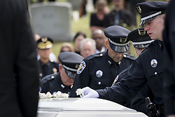 April 4, 2017 - Louisville, Kentucky, U.S. - Officers lay flowers on the casket of Louisville Metro Police Officer Nick Rodman following his funeral in Louisville, Kentucky, Tuesday, April 4, 2017.  Officer Rodman was killed in the line of duty last week during a vehicle pursuit. (Credit Image: © Bryan Woolston via ZUMA Wire)
