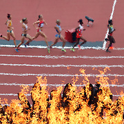 Runners in the Women's 5000m heats pass the Olympic Flame in the Olympic Stadium, Olympic Park, during the London 2012 Olympic games. London, UK. 7th August 2012. Photo Tim Clayton