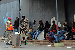 JOHANNESBURG, SOUTH AFRICA - APRIL 18: Soldiers stand next a group of men during a South African Police Service (SAPS) Metro Police and Army supported patrol in Rockey Street, Yeoville. Random searchs and social distancing measures on April 18, 2020 in Johannesburg South Africa. Under pressure from a global pandemic. President Ramaphosa declared a 21 day national lockdown extended by another two weeks, mobilising goverment structures accross the nation to combat the rapidly spreading COVID-19 virus - the lockdown requires businesses to close and the public to stay at home during this period, unless part of approved essential services. (Photo by Dino Lloyd)
