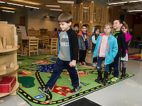 Following their story time Keegan Connelly leads the charge for some outdoor actiivty in the playground at the Huot Technical Center Daycare on Wednesday afternoon.  (Karen Bobotas/for the Laconia Daily Sun)