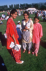 Group of young girls wearing traditional dress standing together at music festival,