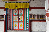 A monastery door and prayer wheels. The monastery is located in the village of Ropa, Himachal Pradesh, India