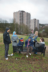 Families chatting by bench with tower blocks behind.
