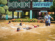 30 SEPTEMBER 2016 - SAI NOI, AYUTTHAYA, THAILAND:  Students at the flooded Wat Boonkannawas School play in the floodwaters that surround their school.  The students swim in the floodwaters that have inundated their playground. The Chao Phraya River, the largest river that runs through central Thailand, has hit flood stage in several areas in Ayutthaya and Ang Thong provinces. Villages along the river are flooded and farms are losing their crops due to the flood. This is the same area that was devastated by floods in 2011, but the floods this year are not expected to be as severe. The floods are being fed by water released from upstream dams. The water is being released to make room for heavy rains expected in October.     PHOTO BY JACK KURTZ