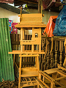 02 NOVEMBER 2016 - BANGKOK, THAILAND:  A partially completed spirit house in the workshop. There used to be 10 families making traditional spirit houses out of teak wood in Ban Fuen, a community near Wat Suttharam in the Khlong San district of Bangkok. The area has been gentrified and many of the spirit house makers have moved out, their traditional wooden Thai houses replaced by modern apartments. Now there is just one family making the elaborate spirit houses. The spirit houses are made by hand. It takes three days to make a small one and up to three weeks to make a large one. Prices start at about $90 (US) for a small one. The largest, most elaborate ones can cost over $1,000 (US). Almost every home and most commercial buildings in Thailand have a spirit house, which is a shrine to the protective spirit of a the land. Spirit houses are also common in Burma, Cambodia, and Laos.       PHOTO BY JACK KURTZ