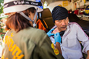 26 DECEMBER 2013 - BANGKOK, THAILAND: A medic helps a Thai rioter shot with a rubber bullet fired by riot police during a riot at the Thai Japan Stadium in Bangkok. Thousands of anti-government protestors flooded into the area around the Thai Japan Stadium to try to prevent the drawing of ballot list numbers by the Election Commission, which determines the order in which candidates appear on the ballot of the Feb. 2 election. They were unable to break into the stadium and ballot list draw went as scheduled. The protestors then started throwing rocks and small explosives at police who responded with tear gas and rubber bullets. At least 20 people were hospitalized in the melee and one policeman was reportedly shot by anti-government protestors.      PHOTO BY JACK KURTZ