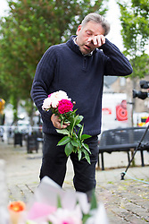 © Licensed to London News Pictures. 17/06/2016. Birstall UK. A man lays flowers at the scene in Birstall market place this morning where MP Jo Cox was murdered yesterday. Photo credit: Andrew McCaren/LNP