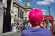 Tourist with shocking pink dyed hair takes pictures of his friends at Trafalgar Square in London, United Kingdom.