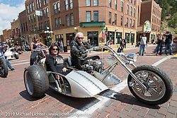 Custom builder Arlen Ness with his wife Bev in the sidecar riding Main Street in Deadwood during the annual Sturgis Black Hills Motorcycle Rally. Deadwood, SD, USA. Monday August 7, 2017.  Photography ©2017 Michael Lichter.