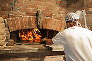 Jamestown, RI - 7 May 2007. Andrea Colognese of The Village Hearth Bakery and Cafe, stoking a fire in the bakery's oven. Colognese built the oven himself.