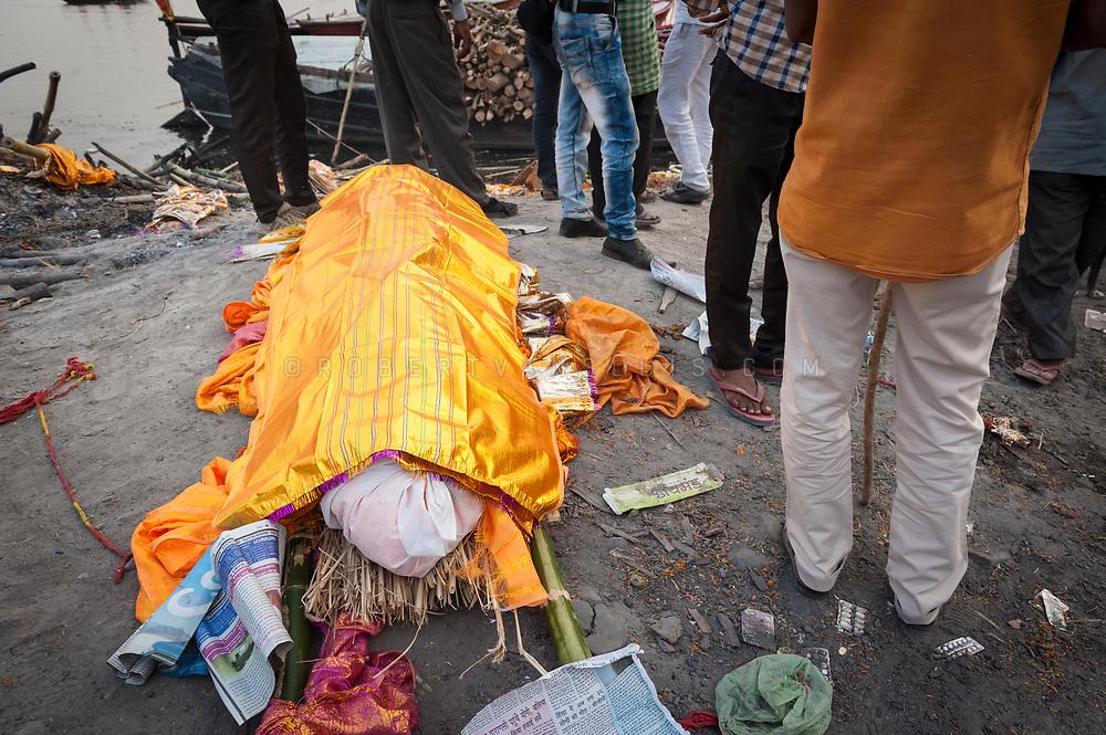A corpse in decorative wrapping lies among bystanders at the Manikarnika cremation ground, Varanasi, India. Photo © robertvansluis.com