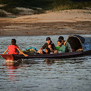 A family heads across the river on a sampan on the Mekong River near Luang Prabang in central Laos.