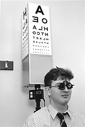 Man taking eye test at opticians standing in front of letter chart,