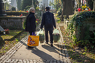 A couple walks filled with plastic bags with flowers on Rakowicki cemetery in Krakow, Poland 2019.