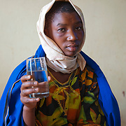 Francoise holds a glass of safe drinking water at the Kisaro Community Clinic in Kisaro Sector, Rulindo District, Rwanda.