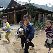 Young Black Hmong children leave school in Lao chai village near Sapa, Northern Vietnam. Sapa and the surrounding highlands are close to the Chinese border in Northern Vietnam and is inhabited by highland minorities including Hmong and Dzao groups. Sapa is now a thriving tourist destination for travelers taking the night train from Hanoi. Sapa, Vietnam. 16th March 2012. Photo Tim Clayton