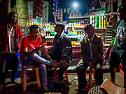 06 AUGUST 2017 - MENGWI, BALI, INDONESIA: Men gather before sunrise for coffee and Balinese snacks in the Bringkit Market in Mengwi, about 30 minutes from Denpasar. Bringkit Market is famous on Bali for its Sunday livestock and poultry market. Hundreds of the small Bali cows are bought and sold there every week. Bali's local markets are open on an every three day rotating schedule because venders travel from town to town. Before modern refrigeration and convenience stores became common place on Bali, markets were thriving community gatherings. Fewer people shop at markets now as more and more consumers go to convenience stores and more families have refrigerators.     PHOTO BY JACK KURTZ