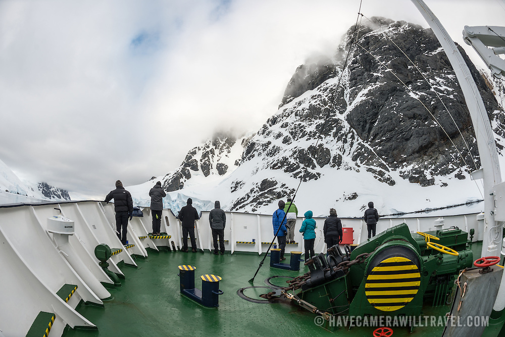 """Passengers on deck admire the dramatic scenery while navigating the Lemaire Channels. The Lemaire Channel is sometimes referred to as """"Kodak Gap"""" in a nod to its famously scenic views."""