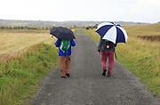 Orford Ness lighthouse Open Day, September 2017, Suffolk, England, UK - two men walking in rain holding umbrellas