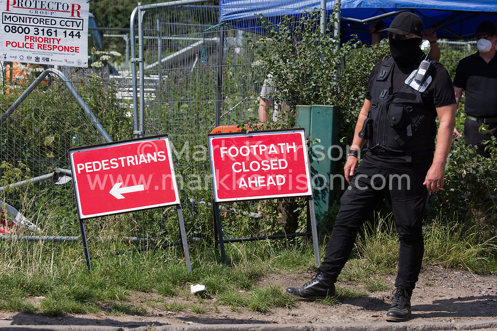 A HS2 security guard observes activists from HS2 Rebellion and Extinction Rebellion UK taking part in a 'Rebel Trail' hike along the route of the HS2 high-speed rail link on 26th June 2020 in Harefield, United Kingdom. The activists, who departed from Birmingham on 20th June and will arrive outside Parliament in London on 27th June, are protesting against the environmental impact of the high-speed rail link and questioning the viability of the £100bn+ project.