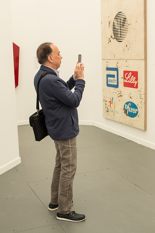 """A man takes a photo of art in the galery of the Peres Projects. On the wall is a diptych titled """"APA Diptych"""" by Mark Flood."""