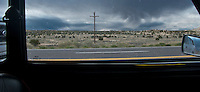 strange cloud and arid landscape through a water spotted auto window and power line along US 550 in NW New Mexico, USA