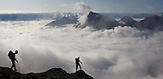 Jim Prager hikes into clouds on the descent from Luna Col to Access Creek, Northern Picket Range, North Cascades National Park, Washington. (He appears twice, as the panorama was stitched from two sequenced photographs).