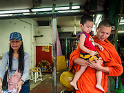 05 JANUARY 2016 - BANGKOK, THAILAND:          A Buddhist monk holds a boy on his alms rounds in an empty shop in the closed Bang Chak Market. The market closed permanently on January 4, 2016. The Bang Chak Market served the community around Sois 91-97 on Sukhumvit Road in the Bangkok suburbs. Bangkok city authorities put up notices in late November that the market would be closed by January 1, 2016 and redevelopment would start shortly after that. Market vendors said condominiums are being built on the land.                   PHOTO BY JACK KURTZ