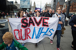 © Licensed to London News Pictures . 25/09/2016 . Liverpool , UK.  People carry a SAVE OUR NHS banner at a Save Liverpool Women's Hospital demonstration along the dockside in Liverpool , on the first day of the Labour Party Conference . Photo credit : Joel Goodman/LNP