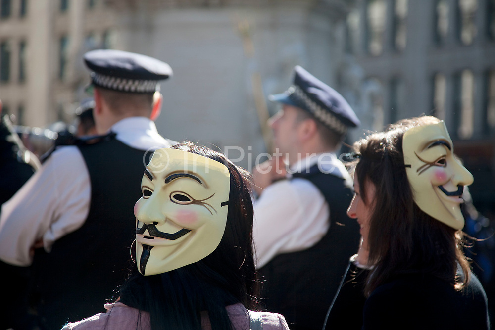 """Masked protesters at the Occupy London protest, October 15th 2011. Protest spreads from the US with this demonstrations in London and other cities worldwide. The 'Occupy' movement is spreading via social media. After four weeks of focus on the Wall Street protest, the campaign against the global banking industry started in the UK this weekend, with the biggest event aiming to """"occupy"""" the London Stock Exchange. The protests have been organised on social media pages that between them have picked up more than 15,000 followers. Campaigners gathered outside  at midday before marching the short distance to Paternoster Square, home of the Stock Exchange and other banks.It is one of a series of events planned around the UK as part of a global day of action, with 800-plus protests promised so far worldwide.Paternoster Square is a private development, giving police more powers to not allow protesters or activists inside."""