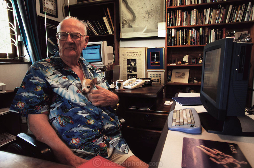 "Colombo, Sri Lanka. Sir Arthur C. Clarke sits at his desk with his one-eyed Chihuahua, ""Pepsi"" tucked inside his shirt. Clarke enjoys telling visitors that this is his reenactment of the alien baby bursting forth from the chest of the astronaut in the sci-fi movie Alien. Published in Stern Magazine, 28 December 2000 issue, pages 76-77. (He has post-polio syndrome) Best known for the book 2001: A Space Odyssey. MODEL RELEASED"