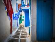 Streets in Mykonos town on the Greek island of Mykonos. Mykonos is a Greek island, part of the Cyclades, lying between Tinos, Syros, Paros and Naxos. There are 10,134 inhabitants  most of whom live in the largest town, Mykonos, which lies on the west coast. The town is also known as Chora (i.e. the Town in Greek, following the common practice in Greece when the name of the island itself is the same as the name of the principal town).<br /> <br /> Mykonos' nickname is The island of the winds. Tourism is a major industry.