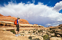 A female hiker observes a large thunderstorm building on the horizon, Squaw Creek Canyon, Canyonlands National Park, Utah, USA.