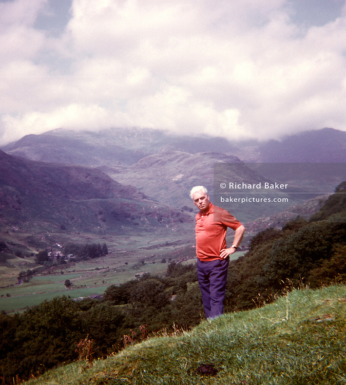 A portrait of a middle-aged man with Welsh mountains and hills in the background, taken on a film camera by an amateur photographer in the 1970s. Standing with hands on hips, the gentleman wearing a short red top is alone on the hillside during a daytrip to the north Welsh mountains in 1973. With the rolling valley and peaks in cloud in the distance, the scene is a tranquil landscape. The picture shows us a memory of nostalgia in an era from the last century.