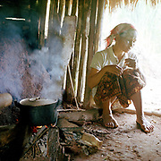 A Khmu woman cooks lunch over an open wood fire in the field shelter on her upland rice field, Ban Chaleunsouk, Luang Namtha Province, Lao PDR.