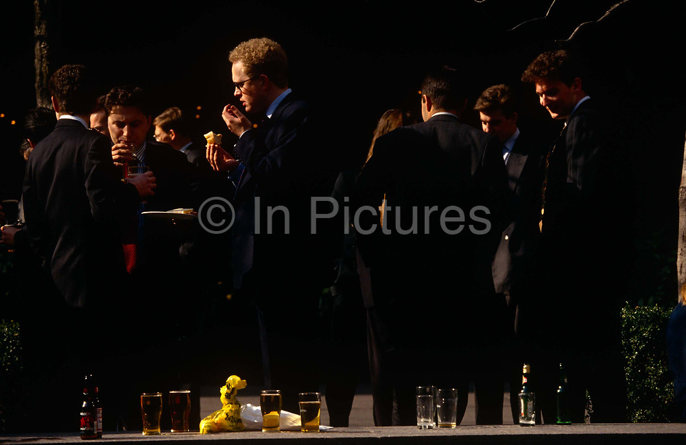 Young businessmen drink and chat outside a City of London pub during a warm lunchtime in Broadgate. With pint glasses lined up on the wall, the suits talk business informally in spring sunshine.