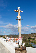 Historic cross crucifixion of Jesus Christ monument in medieval village with the Latin word oblatus,  Mértola, Baixo Alentejo, Portugal, Southern Europe