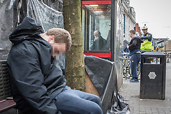© Licensed to London News Pictures . 06/04/2017 . Manchester , UK . A paramedic tends to a man , believed to have consumed spice , in Piccadilly Gardens , as another man consumes a rolled cigarette believed to contain spice , in an adjacent telephone box and a third man lies slumped on a bench . An epidemic of abuse of the drug spice by some of Manchester's homeless population , in plain sight , is causing users to experience psychosis and a zombie-like state and is daily being witnessed in the Piccadilly Gardens area of Manchester , drawing large resource from paramedic services in the city centre . Photo credit : Joel Goodman/LNP