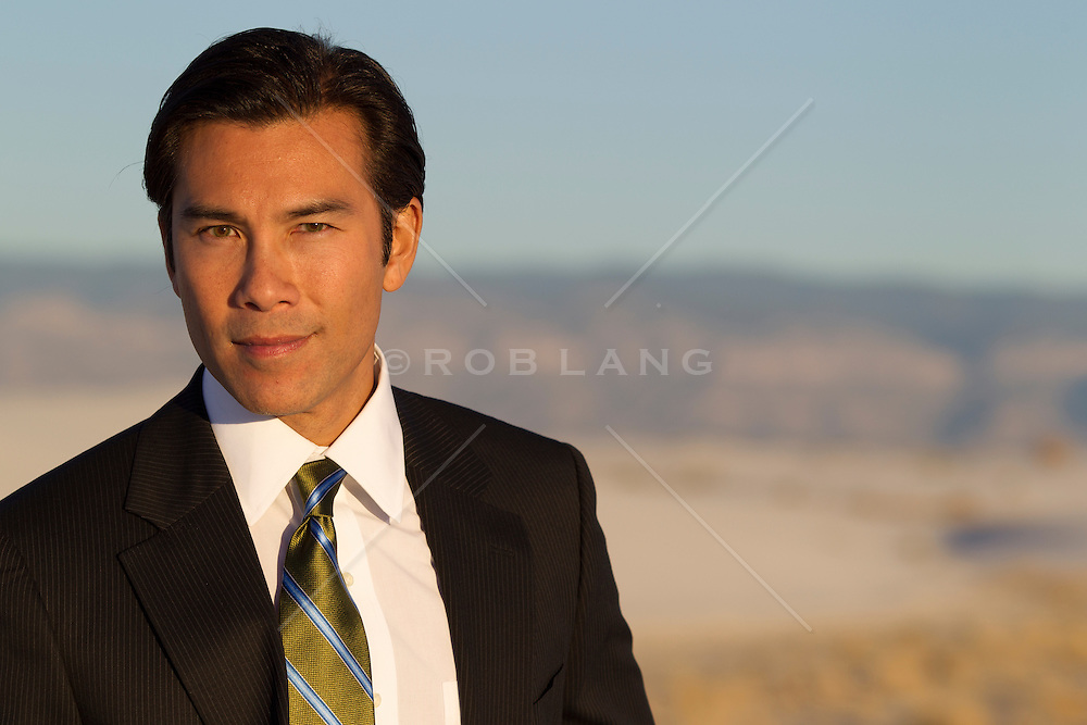 portrait of a handsome Asian American man outdoors in a suit and tie